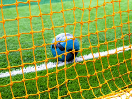 Football in the goal net background