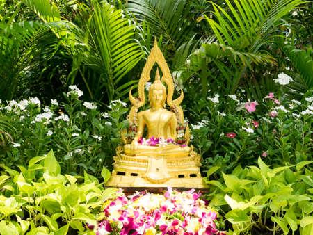 Golden Buddha statue In flower garden