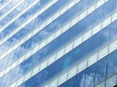 Sky reflecting on glass of windows building Stock Photo