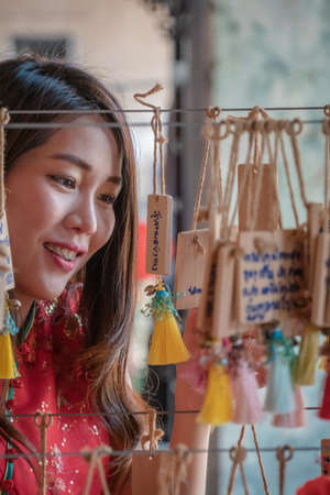 Women looking to lucky knot ornaments for Chinese New Year Chinese, text writing translate into 'lucky and healthy' in english