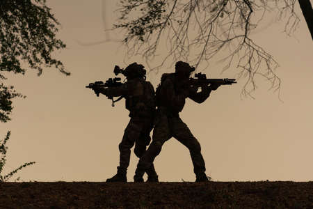 silhouette action soldiers walking hold weapons in jungle Stock Photo