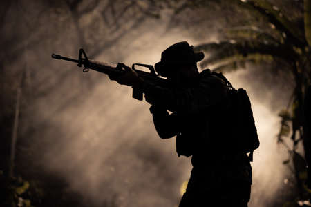silhouette action soldiers walking hold weapons in jungle