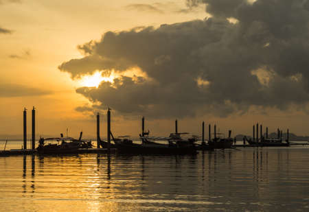 long tail: silhouette sunset at sea  with long tail boat Stock Photo