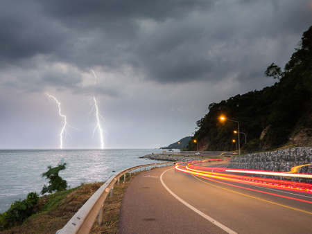 thunderbolt: Noen-nangphaya view point, Landmark at Chanthaburi, Thailand: lightning thunderbolt in sea at twilight with lighting from cars