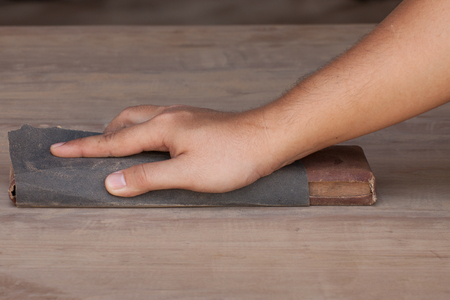 sandpaper: Handyman working with sandpaper on a wooden table