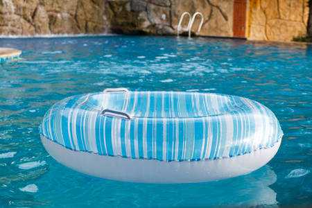 swimming to float: Blue Ring float in swimming pool Stock Photo