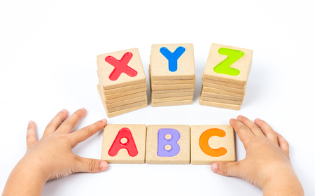 xyz: Kid hands playing wooden alphabets block Stock Photo