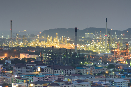Houses and apartments near with Oil refinery industrial at twilight time