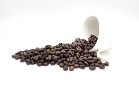 Coffee beans in a falling glass on white background. Reklamní fotografie