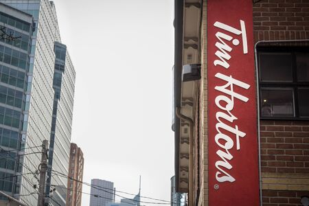 famous industries: Tim Hortons Cafe logo in Downtown Toronto, Ontario, Canada. Tim Hortons is a multinational fast food restaurant based in Canada, icts Known for coffee and donuts Editorial