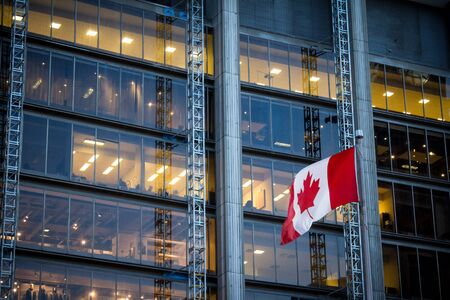 Canadian flag in front of a business building in Toronto Imagens