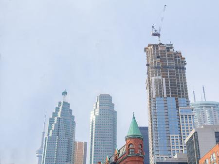 Skyscraper construction site en front of older buildings in downtown Toronto, Ontario, Canada