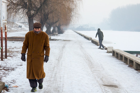 next year: PANCEVO, SERBIA - JANUARY 22, 2017: People walking next to the frozen river Tamis - Timis (a tributary Danube) due to year exceptionnaly cold weather over the Balkans lasting for more than 10 days