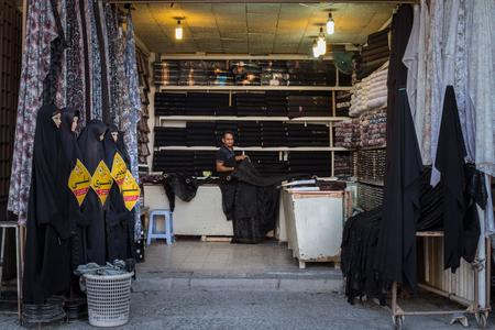veils: ISFAHAN, IRAN - AUGUST 20, 2016: Islamic outfit seller (hijab veils and scarfs in Isfahan bazaar Editorial