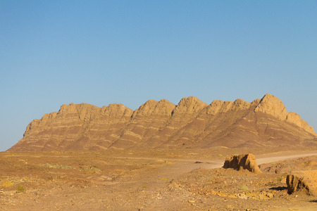 Rock Mountains in the desert near Yazd, IranPicture of rocky hills with a house on the right bottom corner near Yazd, in the center of Iran Stock Photo