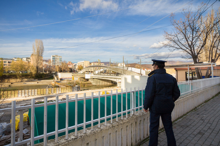 serb: MITROVICA, KOSOVO - NOVEMBER 11, 2016: Kosovo Policeman watching the bridge over the Ibar river, the Albanian Separating from the Serbian portion of the city.