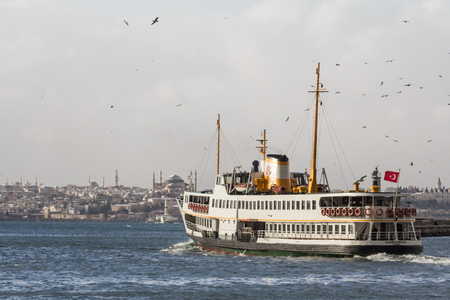 ISTANBUL, TURKEY - DECEMBER 30, 2015: Ferry leaving the harbor district of Kadikoy, Asian side of the city, heading to the European side, Ayasofya mosque can be seen in the background Editorial