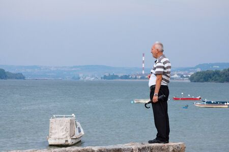 BELGRADE, SERBIA - AUGUST 2, 2015: Old man observing Belgrade center and the Danube from the suburb of Zemun was cloudy day