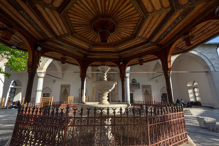 SARAJEVO, BOSNIA HERZEGOVINA - APRIL 17, 2017: Fountain of Gazi Husrev begova Mosque with people praying in the background. The mosque is one of the main landmarks of the Ottoman part of the capital city of Bosnia Editorial