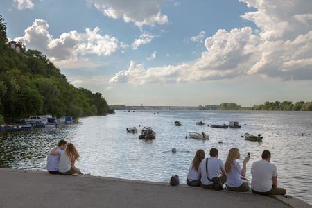 BELGRADE, SERBIA - MAY 13, 2017: Young people sitting on Zemunski Kej at sunset, watching sunset over Danube river