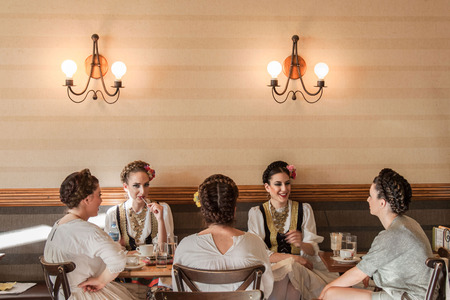 serb: NOVI SAD, SERBIA - JUNE 11, 2017: Young women wearing a traditional Serbian costume having a drink in a local cafe  Picture of 5 girls having a drink in a cafe of Novi Sad, capital city of Voivodina province, Serbia, wearing a traditional Serbian outfit