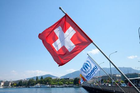 GENEVA, SWITZERLAND - JUNE 19, 2017: Swiss flag and UNHCR flags near leman lake in Geneva. The UNHCR is the agency of the United Nations in charge of handling refugees crises.  Picture of the swiss and UNHCR flags next to each other in Geneva, near the le
