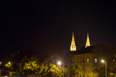 Szeged city center, with a highlight on Szeged Cathedral, seen from a Tosza river during the evening in the summer. Szeged, with the towers of the Catholic Cathedral