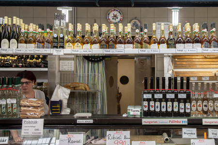 gastro: BUDAPEST, HUNGARY - AUGUST 12, 2017: Bottles of Tokaji wine and other traditional Hungarians drinks and foods for sale in Budapest central market, Nagy Vasarcsarnok  Picture of hungarian products for sale in budapest, with a focus on bottles of the famous