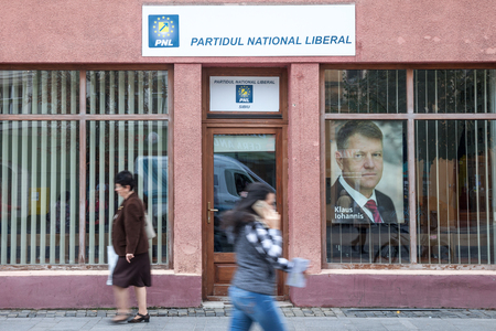SIBIU, ROMANIA SEPTEMBER 22, 2017: People walking in from of the local office of PNL Party (Partidul National Liberal, National Liberal Party), with a picture of Prime Minister Klaus Iohannis in front  Picture of the local office of the PNL Party in Sibiu