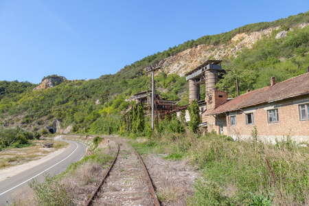 Abandoned mine - quarry near an abandoned railway line in Kucevo, eastern Serbia. Buildings and industrial installations are left to decay  Picture of an abandoned mine and quarry taken in Eastern Serbia, in the city of Kucevo, passing near an abandoned train line, during a summer sunny afternoon