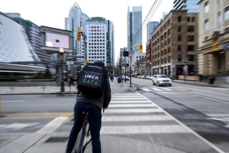 TORONTO, CANADA - DECEMBER 31, 2016: Uber Eats delivery man on a bicycle waiting to cross a street in the center of Toronto, Ontario, with a motion blur effect. Uber Eats is one of the leader of the online food deliveryPicture of a food courrier from Ub Redactioneel