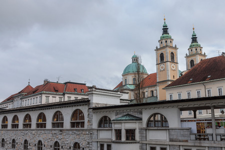 Central Market of Ljubljana, capital city of Slovenia, taken during a cloudy rainy day, with the Ljubljanica river on the foreground and the Ljubljana Cathedral (St. Nicholas Church) in the background
