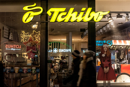 MUNICH, GERMANY - DECEMBER 17, 2017: Tchibo logo on their Munich main shop taken at night. Tchibo is a German chain of coffee retailers and cafés known for its weekly-changing range of other products