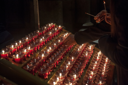 People lighting candles in Notre Dame cathedral in Paris, France. Burning a candle is a usual practice in Catholicism for praying. Stock Photo