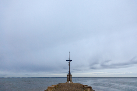 Sailors Cross during a cloudy rainy afternoon in Gujan Mestras, France, on Bassin d'Arcachon. It is a Christ Cross dedicated to the dead sailors who lost their lives on the Atlantic Ocean