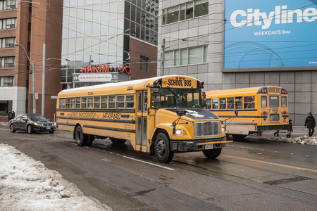 TORONTO, CANADA - DECEMBER 20, 2016: Freightliner FS 65 school bus on a residential part of downtown Toronto, another school bus can be seen in the background Editorial