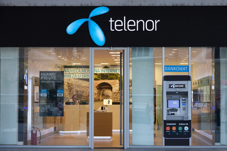 NOVI SAD, SERBIA - JULY 1, 2017: Telenor logo in front of their main shop in Novi Sad, with an ATM from the bank Telenor Banka. Telenor ASA is a Norwegian telecommunications company