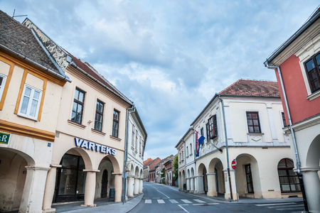 VUKOVAR, CROATIA - MAY 13, 2018: Franjo Tudjman street, the main street of the Slavonia city of Vukovar, in northern Croatia, with its iconic old buildings on a cloudy day