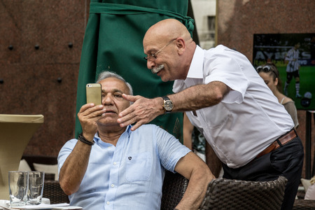 BELGRADE, SERBIA - JUNE 14, 2015: Two young senior men sitting in a cafe looking at an Apple iPhone smartphone, one explaining the second how to use it Editorial