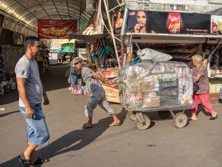 CHISINAU, MOLDOVA - AUGUST 11, 2015: Two delivery persons, a man and a woman, showing efforts pulling a cart in the central market of the capital city of Moldova, Kishinev