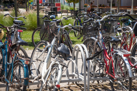 SZEGED, HUNGARY - JUNE 3, 2018: Bicycles raks full of bikes parked by communters near the Szeged market. Hungary is famous for his huge use of bicycle as a transportationPicture of a bike parking lot crowded with bicycles stuffed on racks, during a warm Sajtókép