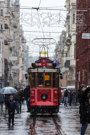 ISTANBUL, TURKEY - DECEMBER 30, 2015: Snowstorm over a tram on Istiklal street, main pedestrian street of Istanbul, Turkey. Istiklal is the main pedestrian street of istanbul