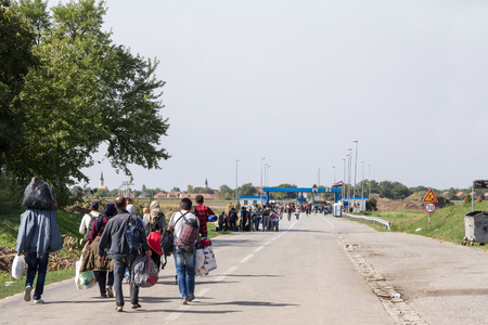 TOVARNIK, CROATIA - SEPTEMBER 19, 2015: Refugees gathering in front of the Serbia-Croatia border crossing of Sid Tovarnik on the Balkans Route, during the Refugee CrisisPicture of a crowd of refugees, mainly from iraq, Syria and Afghanistan, gathering i