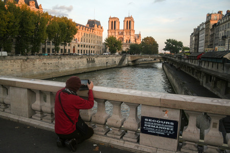 PARIS, FRANCE - OCTOBER 11, 2014: Tourist taking a picture of Notre Dame de Paris Cathedral from a bridge over the Seine River on Ile de la Cite Island. Notre Dame is the biggest gothic cathedral in the world, a symbol of Paris  Picture of Notre Dame de P Redactioneel