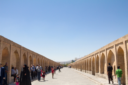 ISFAHAN, IRAN - AUGUST 7, 2015: Iranian people passing by on the Si o Seh Pol bridge on the afternoon in Isfahan, Iran. Also known as Allahverdi Khan Bridge, it is a major landmark of the city   Picture of the iconic bridge of Si o Seh, in the center of I