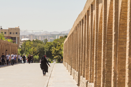 ISFAHAN, IRAN - AUGUST 7, 2015: iranian woman wearing the traditional muslim black veil waling on Si o Seh Pol bridge. Also known as Allahverdi Khan Bridge,  it is a major landmark of the city   Picture of the iconic bridge of Si o Seh, in the center of I