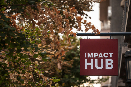 BELGRADE, SERBIA - SEPTEMBER 24, 2018: Logo of Impact Hub on their office in Belgrade. ImpactHub is a startup incubatore providing coworking and office space for social entrepreneurs