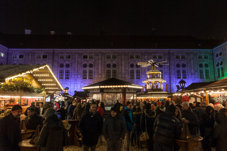 MUNICH, GERMANY - DECEMBER 17, 2017: Crowd gathering on front of the stands of the Munich Christmas market (Christkindlmarkt). Munich Christmas market is one of the oldest in Germany and in the world.  Picture of crowds of people standing in front of the  Editorial