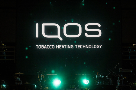 BELGRADE, SERBIA - AUGUST 15, 2018: Iqos logo in front of a bar terrace in Serbia. Iqos, beloning to Philip Morris International, is a tobacco heating cigarette system  Picture of a sign with the Iqos logo taken in front of the terrace of a summer bar Bel Editorial