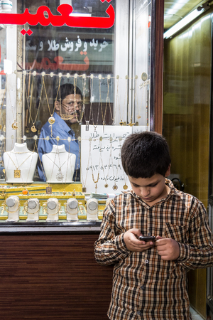 ISFAHAN, IRAN - AUGUST 20, 2016: Young boy playing with a smartphone in front of a jewellery store in Isfahan market, while his older father is looking at him  Picture of a young male child using a smartphone, facing the shop of a jeweler, his father, who